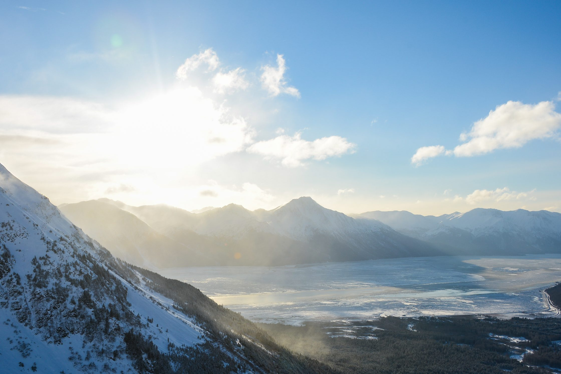 Arctic landscape seen from the top of a snowy mountain with a frozen bay and more mountains in the background.
