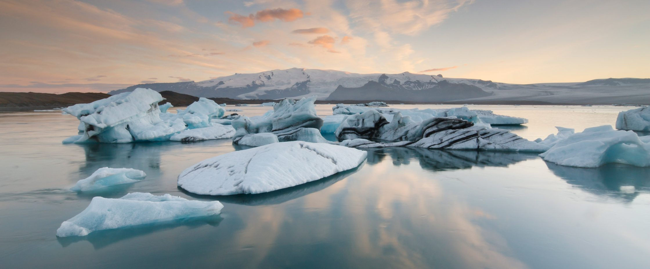 Icebergs floating in the water at sunset.