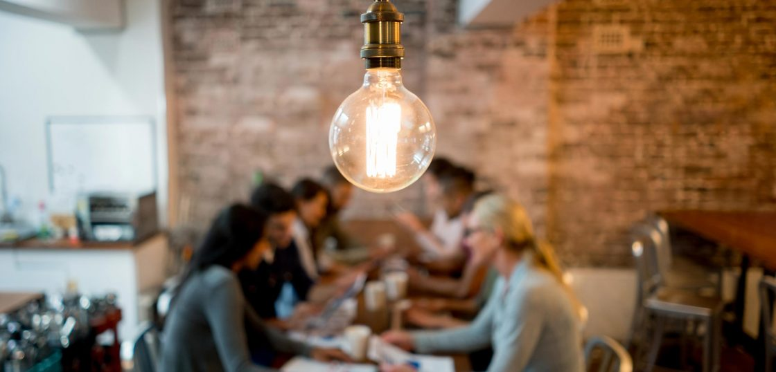 People sitting around meeting table with lightbulb in focus in foreground.